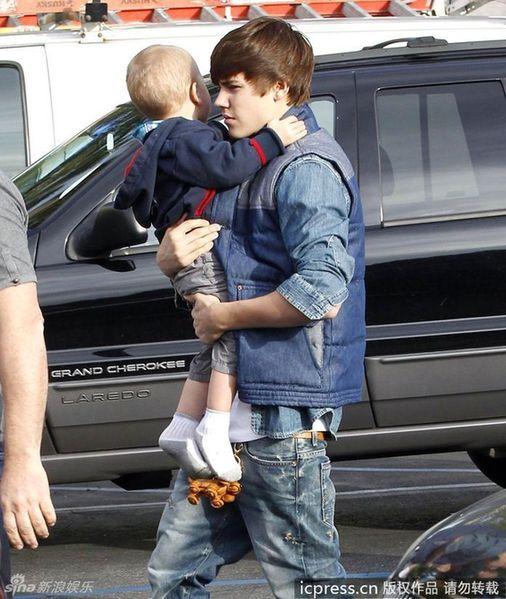 贾斯汀-比伯带着亲戚的孩子和女友赛琳娜-戈麦斯外出逛街.两人抱图片